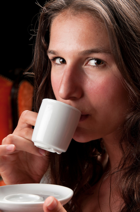 Young woman very serious drinking coffee