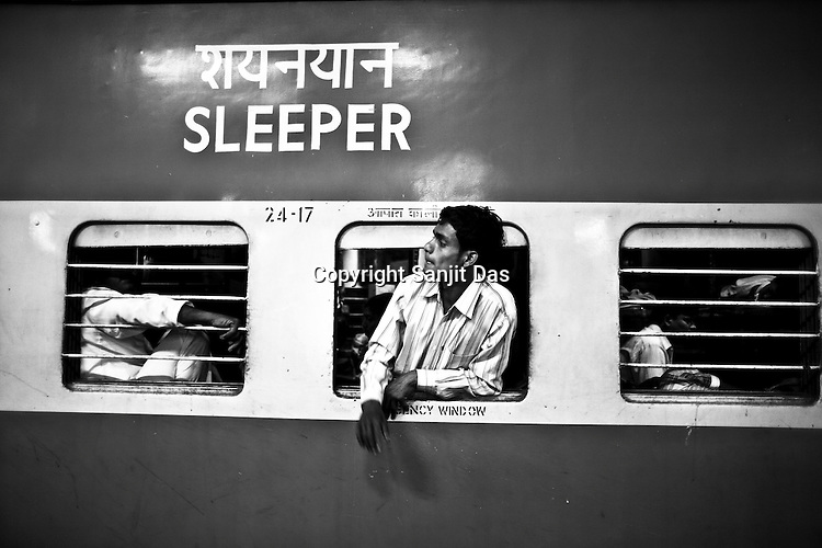 A young passenger is seen sticking his head out of the emergency window of the sleeper class train of the Indian Railways at the Lucknow railway station in Lucknow, Uttar Pradesh, India.