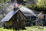 12-year-old Phillip Michael Fontana,  right, gets the upper hand in a water fight with his 13-year-old brother,  John Christopher Fontana, on Saturday, April 3, 2004 in Port Orchard, Wa. The two were trying to beat the heat while playing in the backyard as temperatures reached the low 70's. Jim Bryant photo