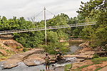 July 6, 2016. Greenville, South Carolina. <br />  The GE Gas Turbine facility is located just miles from downtown Greenville, SC which has recently undergone a renaissance with new parks and restaurants opening. Holly Hensley, of Asheville, NC, jumps from rock to rock at the Reedy River Falls Historic Park. <br />  At the General Electric Gas Turbine factory, engineers  design, produce, test and repair gas turbines for generating electricity. These turbines weigh more than 900,000 pounds and can create internal combustion temperatures up to 2,900 degrees F. Depending on the model, one of the GE turbines can produce enough electricity for half a million American households.