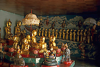 Golden Buddhas under a lampshade inside a pagoda, Bagan, Burma.