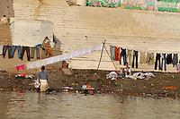 Indian laundrey men washing clothes in a ghat in Varanasi, Uttar Pradesh, India.