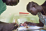 Abak Madut comforts her son Akot while nurse Angelo Ariec pushes her breast milk through a feeding tube to the premature infant in an incubator at the St. Daniel Comboni Catholic Hospital in Wau, South Sudan.