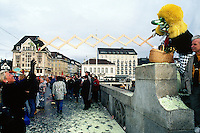 Switzerland. Basel. Fasnacht Carnival. A disguised person with yellow hair and a big nose offers some flowers to a woman on a bridge. © 1997 Didier Ruef