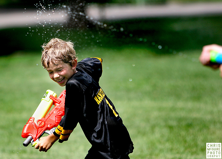 Caden Oliver, 8, plays in a water fight during the Skyhawks Youth Academy flag football camp at City Park on Wednesday, June 25, 2008.