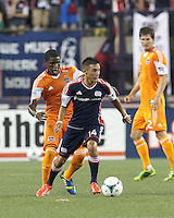 New England Revolution midfielder Diego Fagundez (14) looks to pass as Houston Dynamo defender Kofi Sarkodie (8) pressures. In a Major League Soccer (MLS) match, Houston Dynamo (orange) defeated the New England Revolution (blue), 2-1, at Gillette Stadium on July 13, 2013.