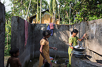 India – West Bengal: Villagers inside a washing point in Pakka Line, one of the villages dotting the Mogulkata Tea Estate, in the Dooars region. Although companies are obliged to provide workers with houses, discounted food rations, schooling, water and health facilities, these services are often non-existent or not up to the standard.