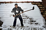 Sain Bobal, a Roma resident of Backo Gradiske, Serbia, shovels snow from the roof of his family's home following a severe winter storm in the region.