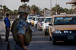Iraqi drivers file past Federal policemen as they search vehicles at a checkpoint in southwest Baghdad August 24, 2010.  .