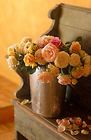 Garden roses fill a silver vase on a wooden bench