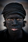 A miner poses for a portrait in Bokapahari in Jharia, Jharkhand, India. The miners work for 9-10 hours a day and make Rs.150 ($3.5) a day loading the coal trucks in the BCCL coal mines in Jharia. Coal fires rage just below the surface of the ground, making it too hot to walk with naked feet, noxious gases spew up from fissures, making the environment toxic. Photo: Sanjit Das