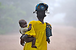 A woman walks with her baby early in the morning in the Congolese village of Wembo Nyama.