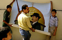 Baghdad, Oct 14, 2002.A poster painter rolls up a Saddam Hussein portrait that will be displayed the next day for the referendum whereby the Iraqi people will decide whether to extend the President's mandate for another 7 years.