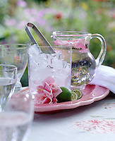 A pink platter with a glass ice bucket and a jug of water decorated with rose petals