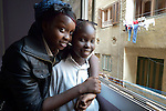 Rebecca Jacob and her sister Martha pose in the window of their fifth floor apartment in Cairo, Egypt. The family fled violence in South Sudan, and today Rebecca and Martha attend classes provided by St. Andrew's Refugee Services, which is supported by Church World Service.