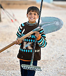 A boy carries a shovel and rake in the Zaatari Refugee Camp, located near Mafraq, Jordan. Opened in July, 2012, the camp holds upwards of 50,000 refugees from the civil war inside Syria, but its numbers are growing. International Orthodox Christian Charities and other members of the ACT Alliance are active in the camp providing essential items and services.