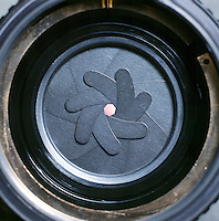 IRIS DIAPHRAGM OF A CAMERA LENS<br /> Changes  the Size of the Aperture or Lens Opening<br /> The iris diaphragm is a series of overlapping metal plates that can fold in on each other or expand out  in a circle, to shrink or expand the diameter of the lens to control the amount of light passing through.