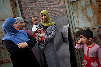 Uighur women stand outside in their neighbourhood in Urumqi.