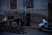 A Uighur woman stands near a partially-demolished building in the Old City section of Kashgar, Xinjiang, China.