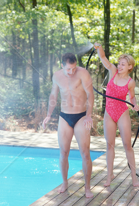 Woman spraying water from a garden hose on a man in a speedo by a swimming pool