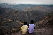 An overview of the coal mines of Borapahari in Jharia, Jharkhand, India. Coal fires rage just below the surface of the ground, making it too hot to walk with naked feet, noxious gases spew up from fissures, making the environment toxic. Residents who live above the furnace make $2 a day collecting small chunks of coal they sell to illegal middlemen. One or two houses collapse annually into vast underground caverns left unfilled by abandoned mining operations. Photo: Sanjit Das