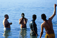 Jordan. Dead sea. Jordanians tourists (muslim boy) takes a bath, swimm and float on the salt water. They cover their body and face with mud for healthy reasons and enjoy themselves on a sunny friday afternoon. Friday is the day off (resting day) in the arabian culture. On the other side of the sea is Palestine and the West Bank (Occupied Territories by Israel). © 2002 Didier Ruef