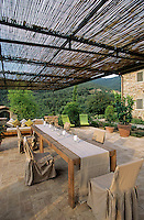 A long wooden dining table on the terrace with a wooden canopy protecting the area from the sun