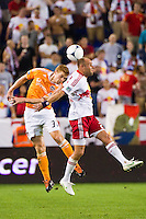 Andre Hainault (31) of the Houston Dynamo goes up for a header with Joel Lindpere (20) of the New York Red Bulls. The New York Red Bulls defeated the Houston Dynamo 2-0 during a Major League Soccer (MLS) match at Red Bull Arena in Harrison, NJ, on August 10, 2012.