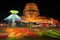 AUGUSTA, NJ - AUGUST 13: Colorfully illuminated rides, including the Sizzler in the foreground, spin against the night sky during the New Jersey State Fair on August 13, 2010 at the Sussex County Fairgrounds, Augusta, New Jersey.