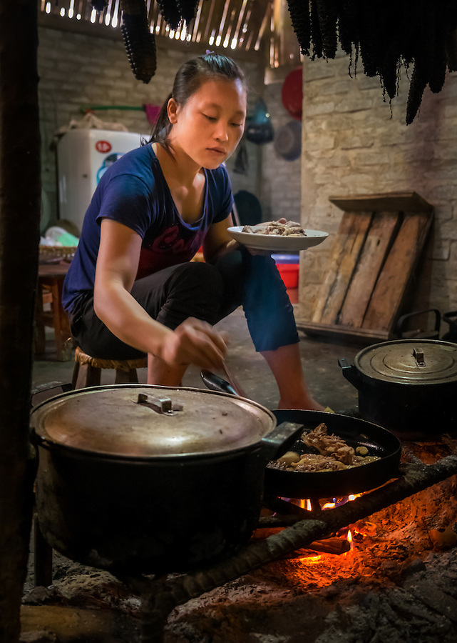 SAPA, VIETNAM - CIRCA SEPTEMBER 2014:  Young woman from the Red Dao minority cooking in a typical house of the Ta Phin Village near Sapa, North Vietnam.