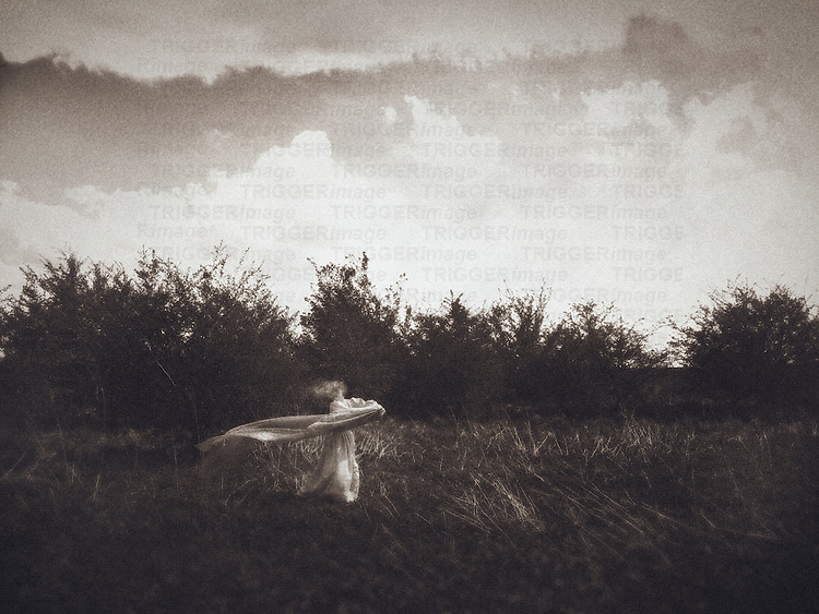 A ghostly figure of a woman with a long veil dancing on the field, with small trees in the background and a cloudy sky.