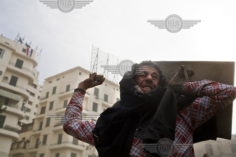 Aa anti-government protester, holding a makeshift shield, hurls a rock at pro-Mubarak supporters just outside Tahrir Square. 25 January 2011 saw the beginning of a nationwide 18 day protest movement that eventually ended the 30-year rule of Hosni Mubarak and his National Democratic Party.