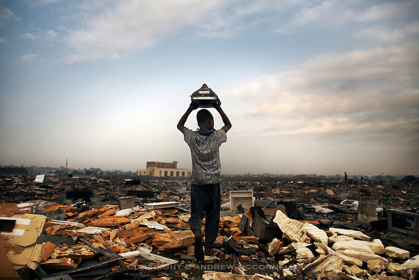 A child is about to break apart a CRT monitor to salvage metal from inside, at Agbogbloshie dump in Accra, Ghana.