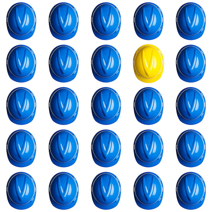 yellow helmet surrounded by various blue hardhats