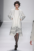 Model walks runway in an ivory wool boucle princess a-line coat+dress bordered w/ivory+black reembroidered french lace sprinked w/ombre beads, from the Zang Toi Fall 2012 &quot;Glamour At Gstaad&quot; collection, during Mercedes-Benz Fashion Week New York Fall 2012 at Lincoln Center.