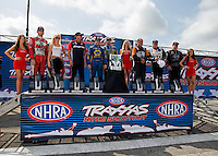 Sept. 1, 2013; Clermont, IN, USA: The Traxxas girls (in red dresses) pose with NHRA funny car driver (L-R) Jack Beckman, Courtney Force, Cruz Pedregon, Ron Capps, Matt Hagan, Johnny Gray, John Force and Tim Wilkerson who will run in the Traxxas Nitro Shootout during qualifying for the US Nationals at Lucas Oil Raceway. Mandatory Credit: Mark J. Rebilas-