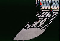 Father and son stand in the shadow of a gate at the Ballpark In Arlington, April 1996. Photograph © 1996 Darren Carroll
