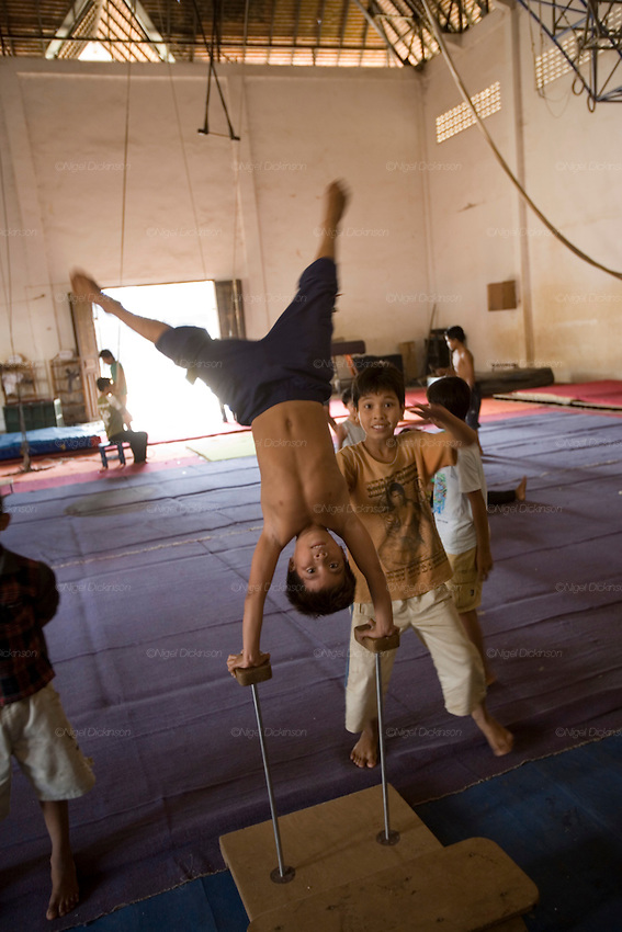 Sarak learning to be an acrobat at the circus school nearby his home in Battambang province, Cambodia..Sarak is a young Khmer boy who comes from a peasant family, living in a small village in Battambang Province, in northwest Cambodia. He lives with his mother and father, brothers, sister, cousins and his aunts and uncles. they are a big family. Sarak loves to learn how to be an acrobat in the local circus school, and spends as much time as he can doing headstands and somersaults with his friends. To be honest, he is a bit of a scoundrel, and enjoys head butting the billy goat, but he makes up by feeding all the animals in his parents little farm. His mother works at the fishmarket in Battambang town, whilst his father sells icecreams. They don't have very much money, not even electricity, so he and his brothers and sisters do their homework under candlelight. He likes to take trips, with his mother and cousins, on his uncle's scooter.