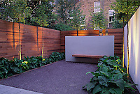 General over view of tiny city garden at dusk with two lit Morroccan lanterns on a rendered wall