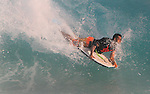 A boarder drops into a wave at Sandy Beach in Hawaii.