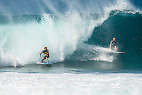 PIPELINE, Oahu, Hawaii (Tuesday, December 10, 2013) John John Florence (HAW) and Mick Fanning (AUS).   - The 2013 Billabong Pipe Masters in Memory of Andy Irons resumed today in six foot (2 metre) barrels and there was no shortage of drama in the ASP World Title race between Mick Fanning (AUS), 32, and Kelly Slater (USA), 41. There was also a shift in the Vans Triple Crown of Surfing Rankings as well as qualification developments for the 2014 WCT.<br /> <br /> The Billabong Pipe Masters represents the pinnacle of the 2013 ASP World Championship Tour, deciding the ASP World Title, Vans Triple Crown of Surfing, and final slots for 2014 ASP WCT qualification.<br /> <br /> Mick Fanning, two-time ASP World Champion and current No. 1, dominated his Round 3 clash with wildcard Kaimana Jaquias (HAW), 20, but unexpectedly erred in his three-man Round 4 heat against John John Florence (HAW), 21, and Nat Young (USA), 22. A last minute paddle battle with heat leader Florence in the closing seconds of the match took him from second to third and now pits him against one of the best Pipeline surfers in the world: C.J. Hobgood (USA), 34, in Round 5. Meanwhile, Slater skips Round 5 and heads straight to the Quarterfinals after his Round 4 win.<br /> <br /> Clearly disappointed with his misstep, Fanning couldn&rsquo;t leave the beach fast enough and wasn&rsquo;t prepared to talk about how this affects his approach to the final day of competition.<br /> <br /> Kelly Slater was electric in his bid for a historic 12th ASP World Title, earning the high heat-totals of both Round 3 and 4. Slater tore past Mitch Crews (AUS), 23, with a 17.66 out of 20 heat total for incredible Pipeline and Backdoor barrels and backed up the performance with a 17.50 out of 20 in Round 4.<br /> Photo: joliphotos.com