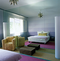 A colour field painting by Nicholas Alvis Vega adorns the wall of this bedroom and is reflected in the mirrored wall which faces the contemporary bed