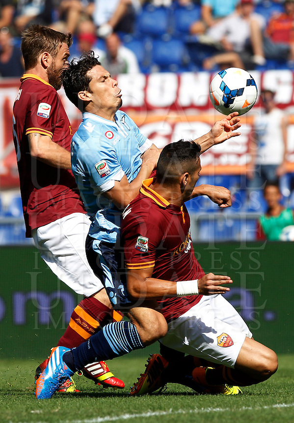 Calcio, Serie A: Roma vs Lazio. Roma, stadio Olimpico, 22 settembre 2013.<br /> Lazio midfielder Hernanes, of Brazil, center, fight for the ball against AS Roma defender Leandro Castan, also of Brazil, right, and midfielder Daniele De Rossi, during the Italian Serie A football match between AS Roma and Lazio, at Rome's Olympic stadium, 22 September 2013.<br /> UPDATE IMAGES PRESS/Isabella Bonotto