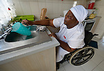 Jennifer Mhlanga suffered a spinal injury in a bus accident, and today uses a wheelchair to get around her home and neighborhood in Harare, Zimbabwe. Here she prepares food in her kitchen. Mhlanga's wheelchair, which was carefully fitted to her individual needs, was provided by the Jairos Jiri Association with support from CBM-US.