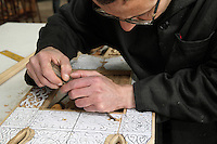 An apprentice carving wood using a drawn stencil in a workshop in sculpted woodwork at the Artisan School or Dar Sanaa, founded 1919 under the Spanish Protectorate of Morocco, which teaches the traditional art and craft skills of woodwork, zellige, sculpted plaster, leatherwork, etc, in Tetouan on the slopes of Jbel Dersa in the Rif Mountains of Northern Morocco. Tetouan was of particular importance in the Islamic period from the 8th century, when it served as the main point of contact between Morocco and Andalusia. After the Reconquest, the town was rebuilt by Andalusian refugees who had been expelled by the Spanish. Picture by Manuel Cohen