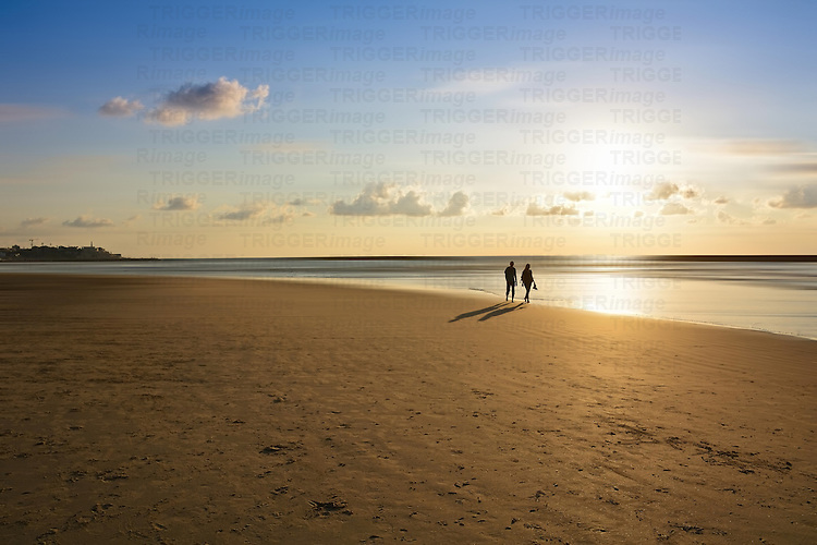 Conceptual beach scene with young couple walking on sand at sunset