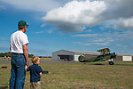 Pilot Ray Ballantyne, who retired from the FAA, and his young grandson watch as a 1920 Travel Aire biplane taxis out for a flight. The boy loves to fly with grandpa in his plane!