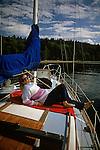 Woman enjoying sun on sailboat moored off Blake Island in Puget Sound Seattle Washington State USA