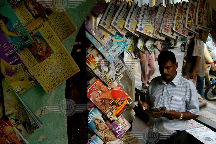 Multi-ethnic society. Indian man reading a magazine at a newsstand, displaying Malay, Indian and Chinese language publications, in Little India.