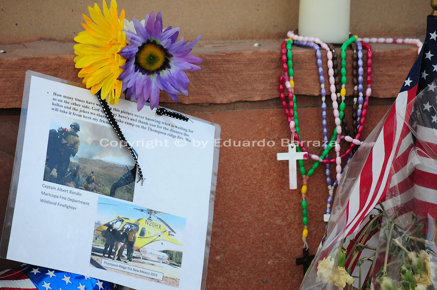 Phoenix, Arizona. July 3, 2013.  A small makeshift memorial for the 19 Arizona firefighters who died on June 30 battling the Yarnell Hill wildfire was built outside the Forensic Science Center in Phoenix, where autopsies are being conducted. Religious objects and signs like this written by Captain Albert Bandin were placed on a exterior wall of the Forensic Science Center in the city Phoenix paying tribute to the 19 fallen firefighters. Photo by Eduardo Barraza © 2013